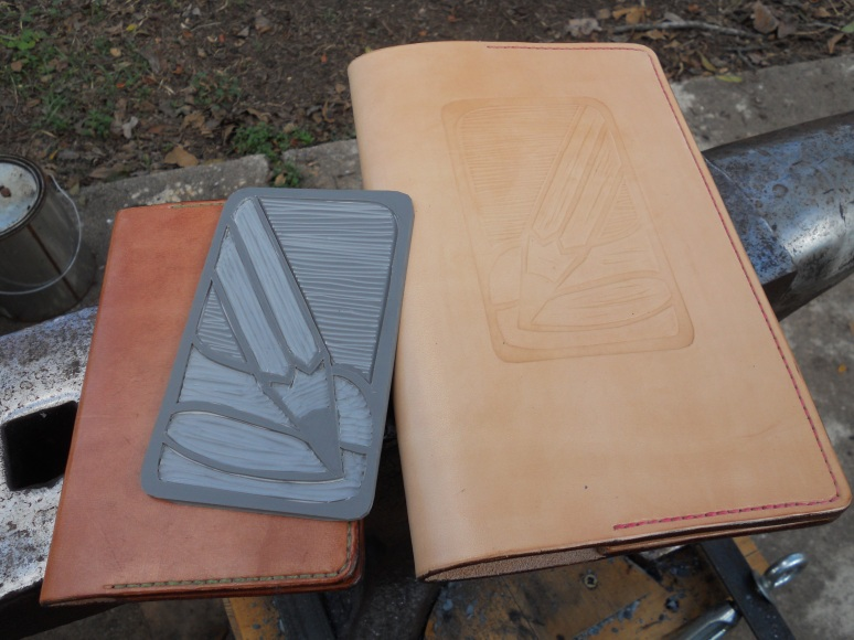 The two new Moleskine covers I made and the linoleum cut I used to create the embossed image.