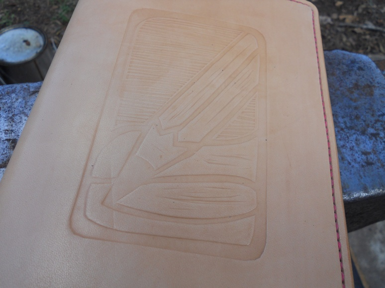 The detail from the linoleum cut has transferred very well to the leather.